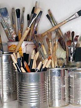 Botes de lata con pinceles y lápices